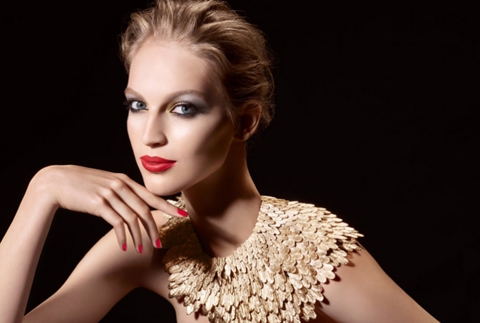 collar-like decoration made of gold, worn by a slim young woman, with short slicked back blonde hair, and holiday makeup, red lipstick and pale blue eye shadow