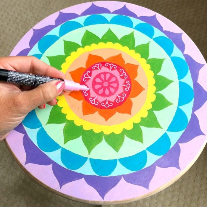 flourishes drawn in white marker, decorating a flower mandala, in rainbow colors, painted on a round wooden stool, diy room decor, hand holding a marker