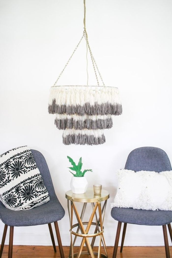 two dark grey modern chairs, and a small metallic coffee table, near a DIY chandelier, decorated with handmade tassels, room makeover, in a few easy steps