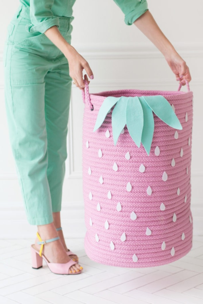 how to decorate a bedroom, slim woman dressed in teal trousers, and matching shirt, holding a large pink basket, decorated like a giant strawberry