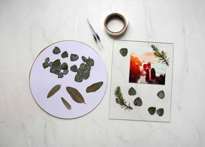 clear glass with a photo, and dried leaves placed on top, near some masking tape, tweezers and more dried plants, dorm wall décor