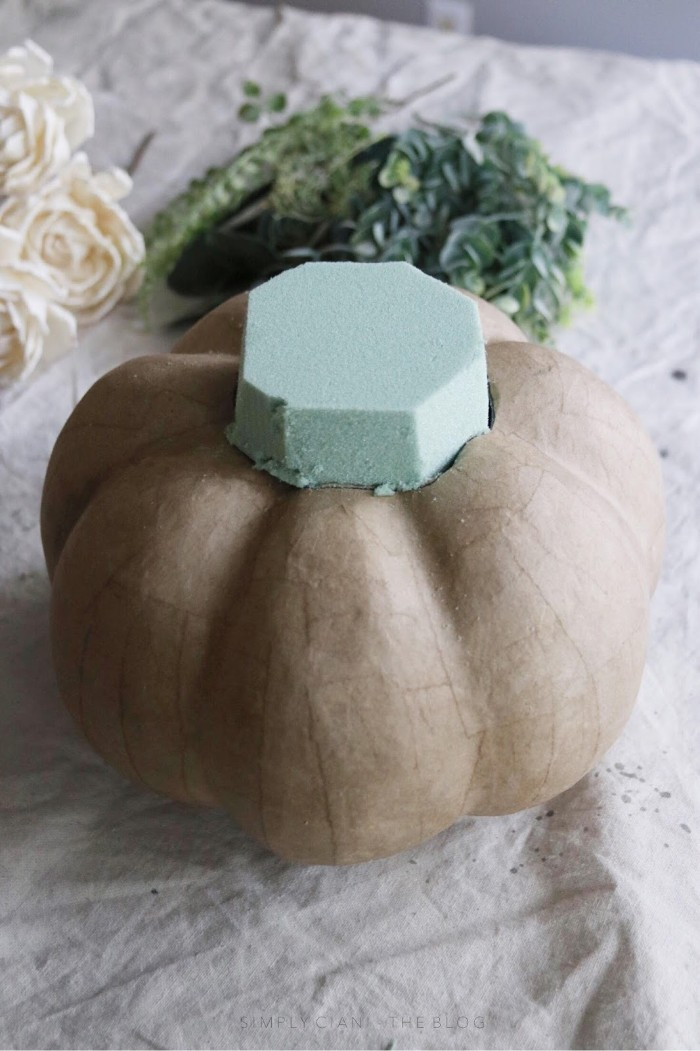 shaping a mint green florist sponge, and placing it inside a hole, cut on top of a beige, papier mache pumpkin, dollar store crafts, to try at home