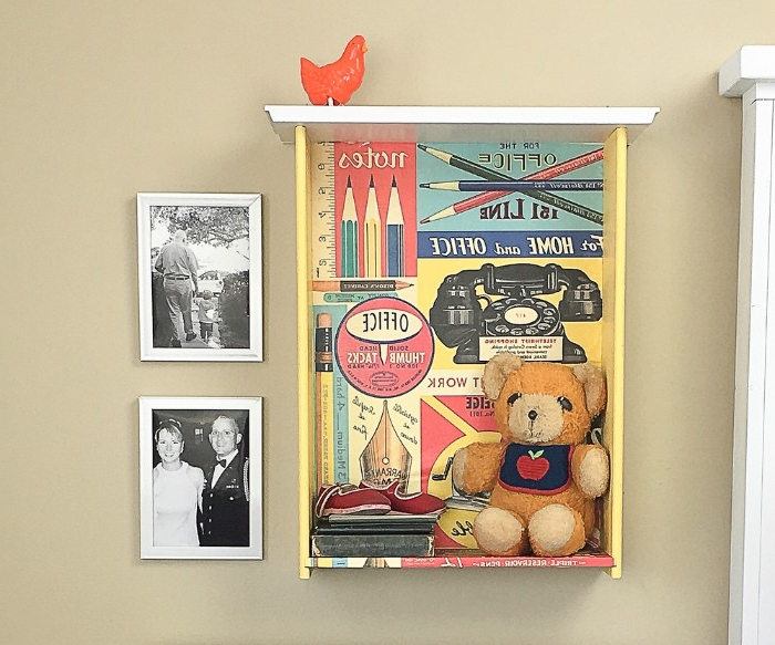 old teddy bear, baby shoes and other items, inside a used drawer, decorated with decoupage, and hung on a beige wall, near two black and white photos