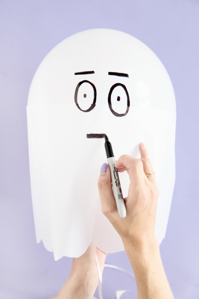 face drawn with black permanent marker, on a white balloon, decorated with white paper, to look like a ghost
