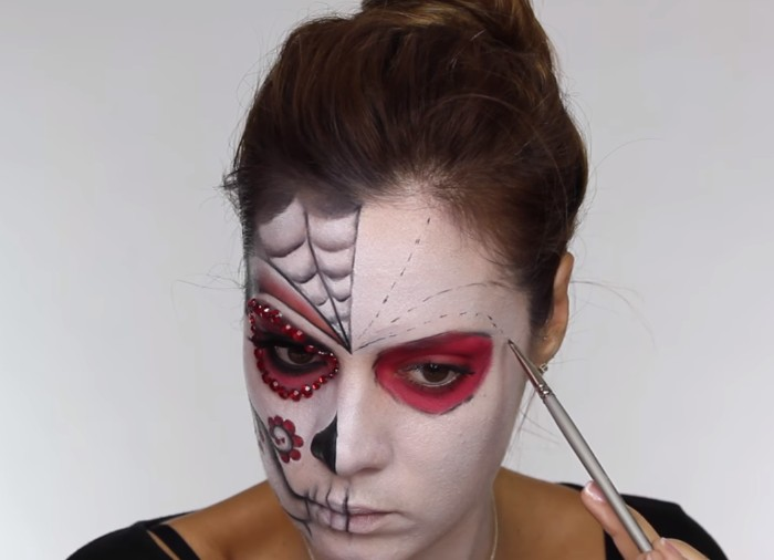 spider web details, and floral motifs, painted on the face of a young woman, covered in white paint, skeleton face paint, sugar skull style
