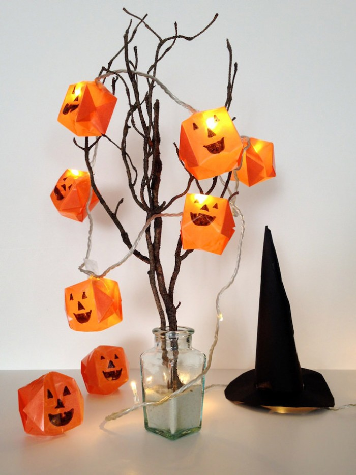 lit pumpkin fairy lights, string lights covered in orange, paper origami shapes, with hand-painted jack-o-lantern faces, placed on dried tree branches in a vase
