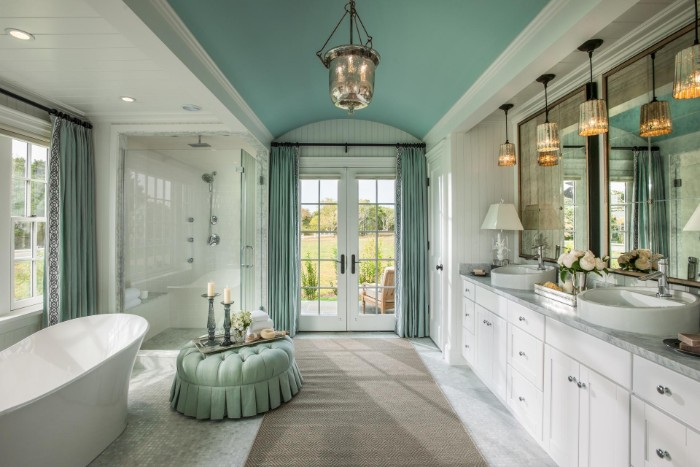 spacious classic bathroom, in duck's egg blue and white, with a beige rug, master bathroom ideas, tub and shower cabin, several different lamps