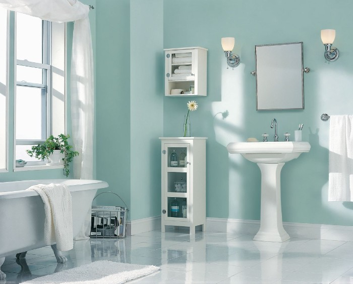 light blue walls, inside a bright room, with a bathtub, a sink and two small cupboards, bathroom color schemes, smooth white tiled floor