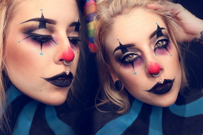 purple eye shadow, with black and blue details, black lipstick and a red nose, clown face paint, worn by a blonde woman
