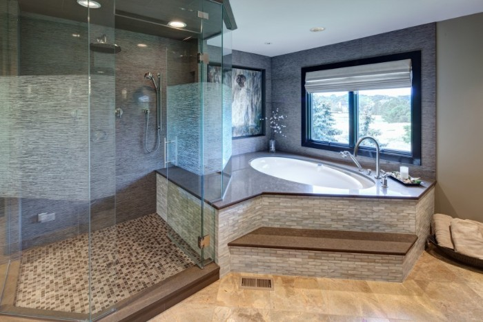 roomy glass shower cabin, near an elevated oval bathtub, master bathroom remodel, light beige laminate floor, window and mosaic tiles