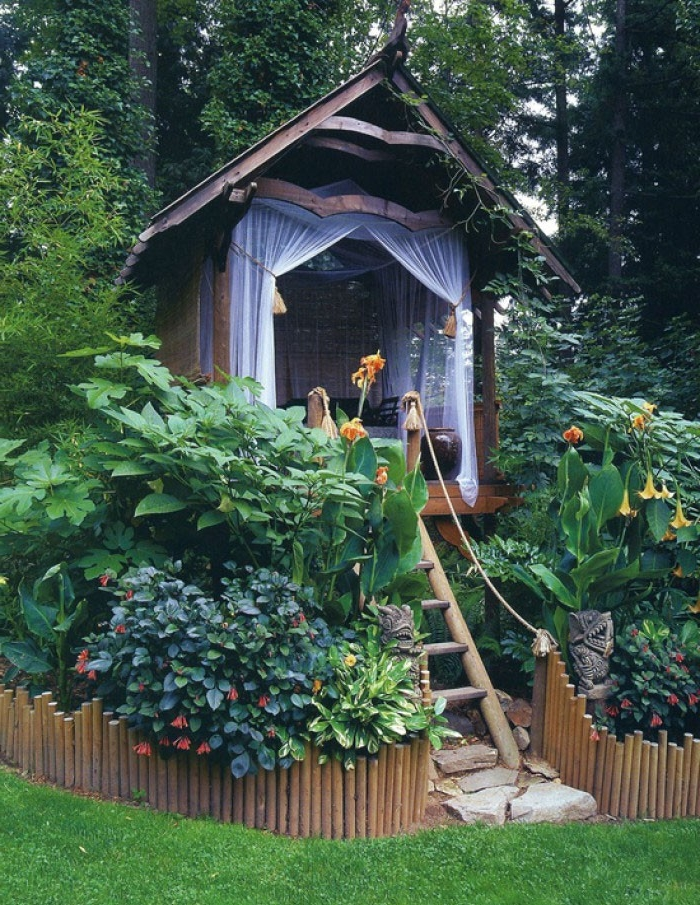 sheer curtains in white, on a small tree-house style shed, accessible via a wooden ladder, and surrounded by various shrubs and flowers