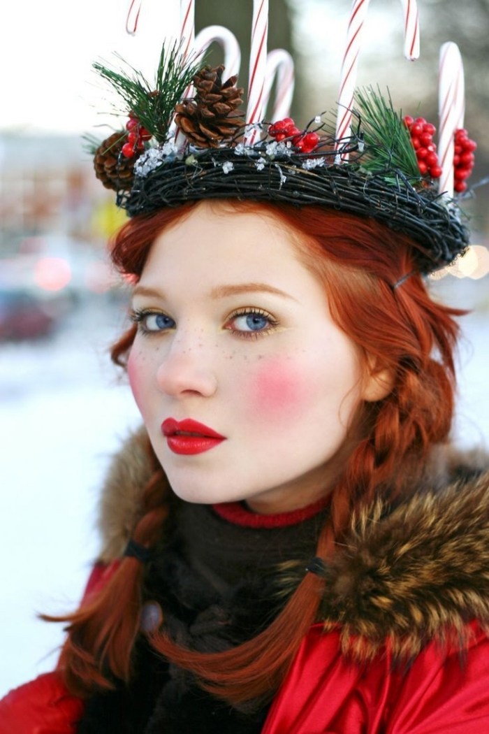 doll-like makeup, with bright red lipstick, and intense pink blush, christmas makeup ideas, worn by a red-haired young woman, with a christmas wreath on her head