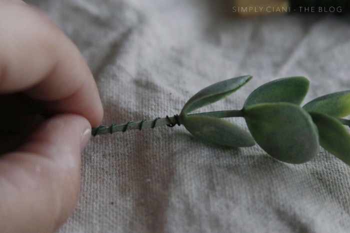 wire wrapped around the stalk, of a small green plastic plant, held by a pale hand, dollar store crafts, seen in extreme close up