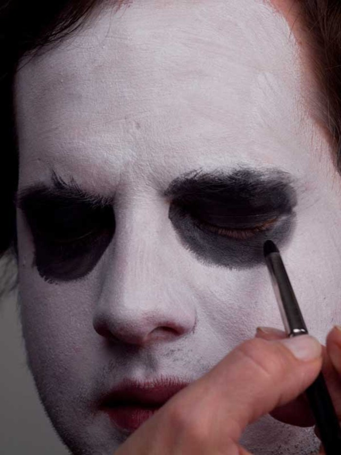 joker halloween makeup tutorial, adding black eye shadow, around the closed eyes, of a man with a face covered in white paint