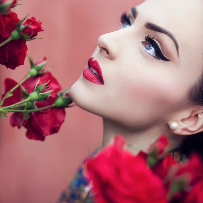 bold black eyeliner, worn by a pale young woman, with glossy red lipstick, and pale pink blush, christmas makeup, several red roses nearby