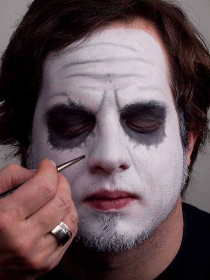 lots of wrinkles, painted with grey, on the face of a young man, wearing white makeup, and grey eyeshadow around his eyes, clown face paint, batman joker look