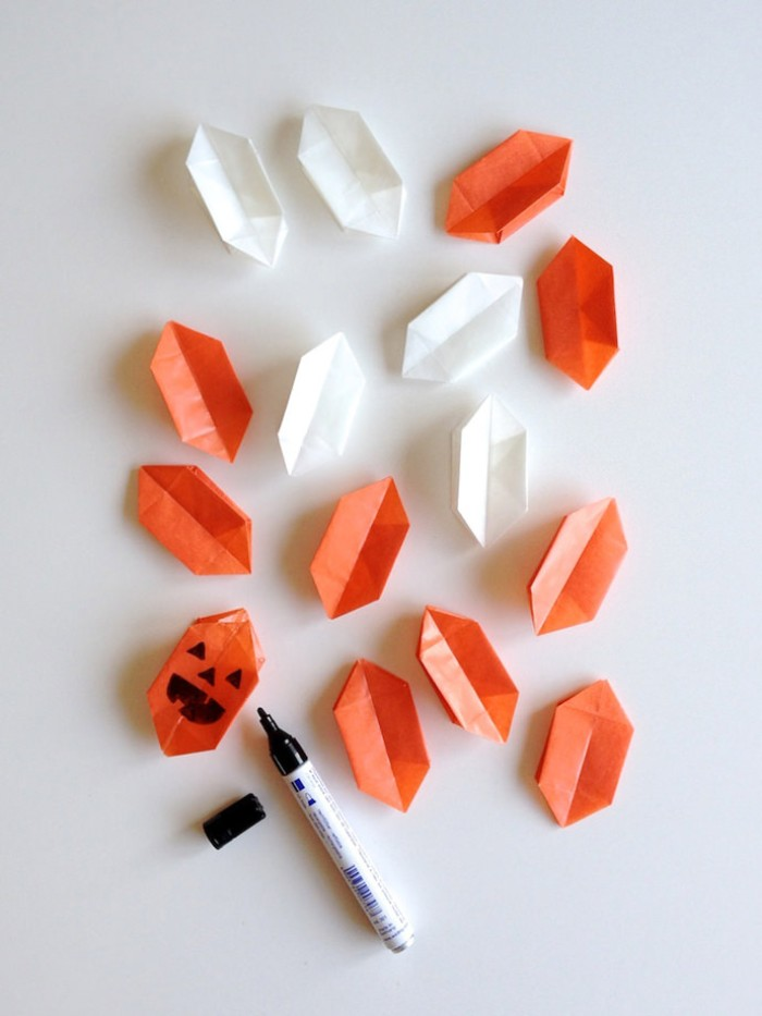 fifteen paper origami shapes, in orange and white, one shape has a hand-drawn, jack-o-lantern face, done in black marker