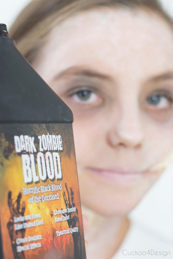 facepaint ideas, close up of a black bottle, with the inscription dark zombie blood on the label, smiling young girl, with pale makeup in the background