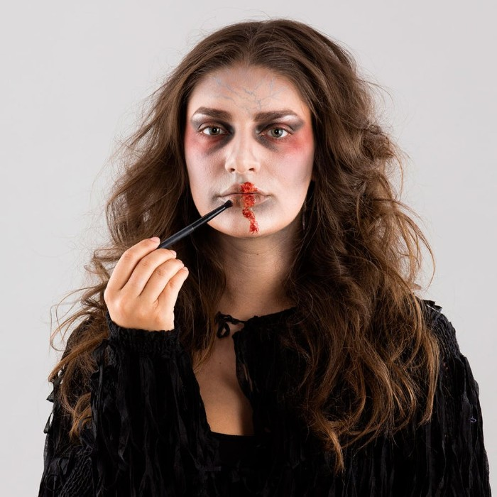 faux blood added with a brush, on a the lips of a woman, with zombie face paint, wearing a black costume