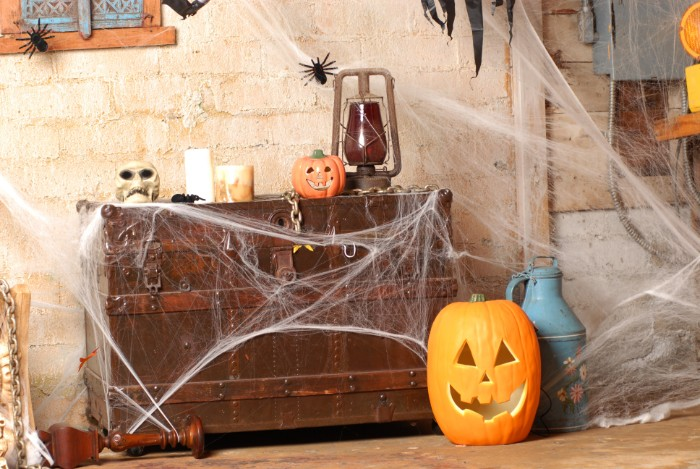 massive brown wooden chest, decorated with fake cobwebs, a skull and an antique gas lamp, candles and black plastic spiders, haunted house decorations, jack-o-lantern ornament on the floor