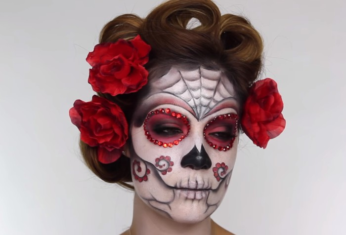 finished sugar skull face paint, worn by a young woman, with curled brunette hair, decorated with three red faux flowers, halloween face paint, in white and black and red, decorated with rhinestones