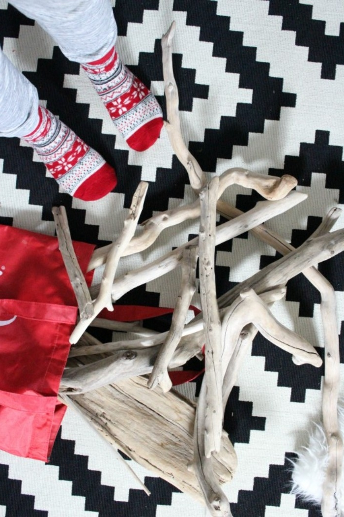 fair isle christmas themed socks, worn by two feet, standing on a black and white tiled floor, next to a pile of pale driftwood, how to decorate your room, using natural materials