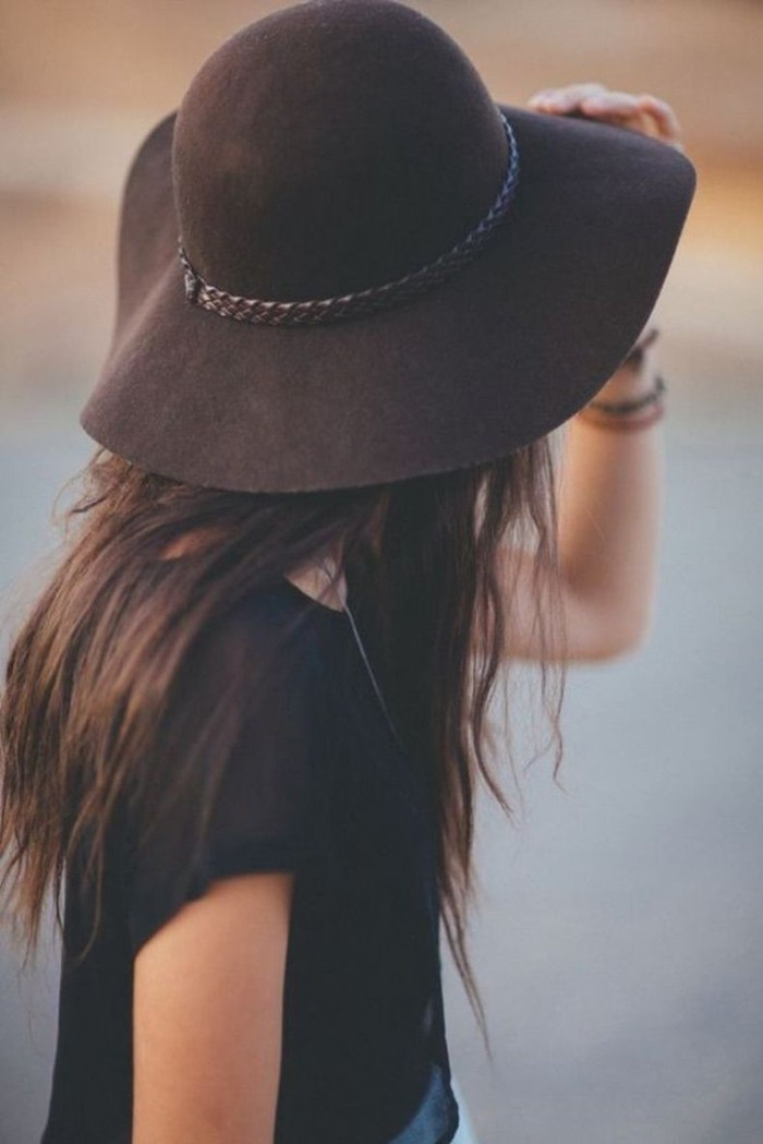 large dark brown felt hat, with woven leather detail, worn by a brunette woman, with long hair, and a black t-shirt