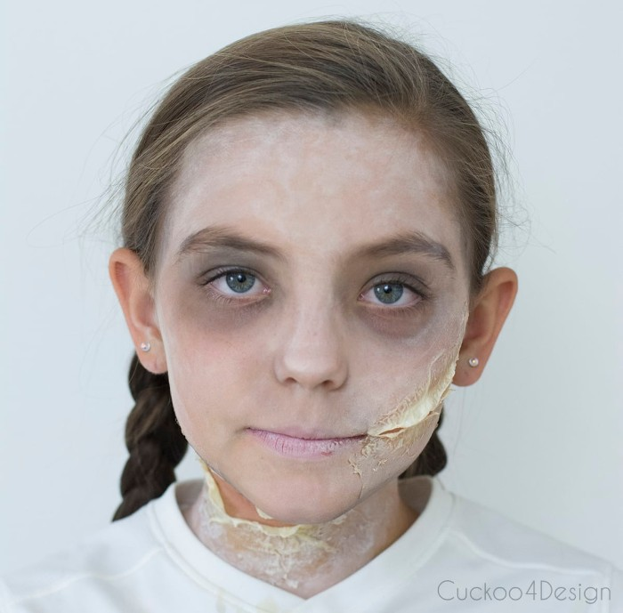t-shirt in white, worn by a young girl, with face covered in white powder, fake scars on her cheek and neck, scary face paint, grey eye shadow around her eyes