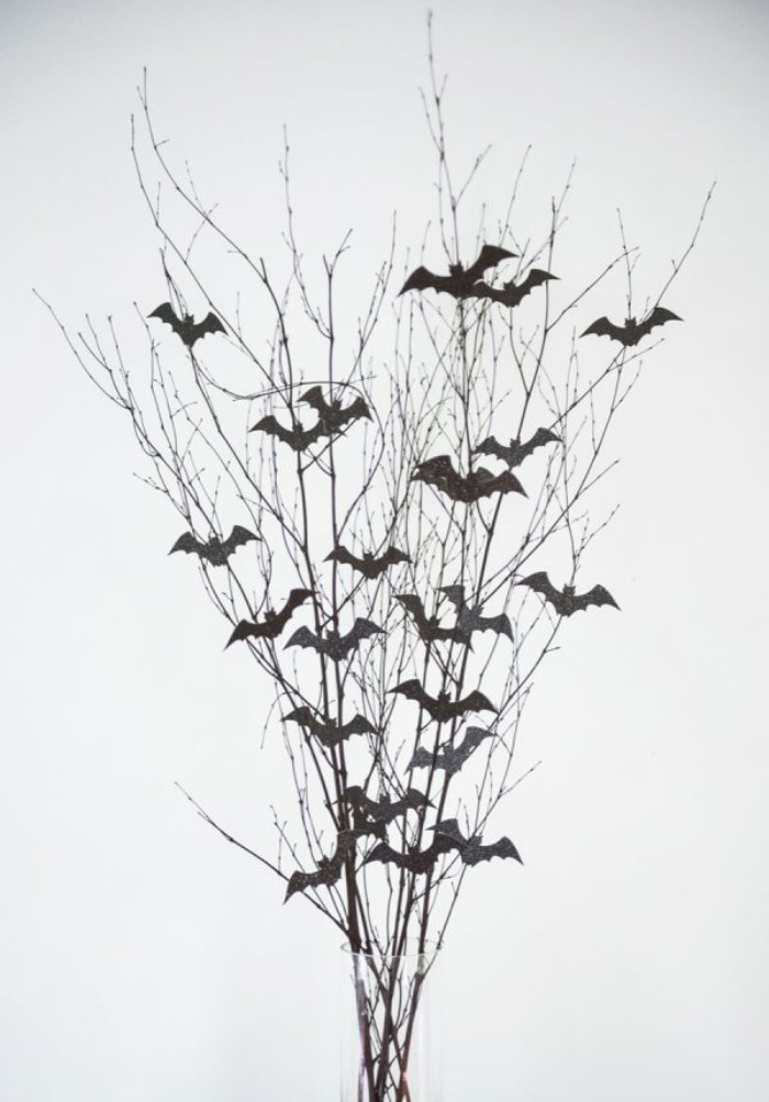 thin dried branches, decorated with small bath shapes, cut out from black card, in a clear glass vase, on a white background