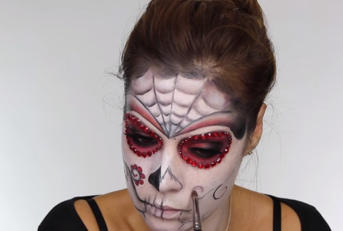 drawing a floral motif, on the face of a young woman, covered in white, and pink paint, with black details, skeleton face paint, creating a sugar skull costume