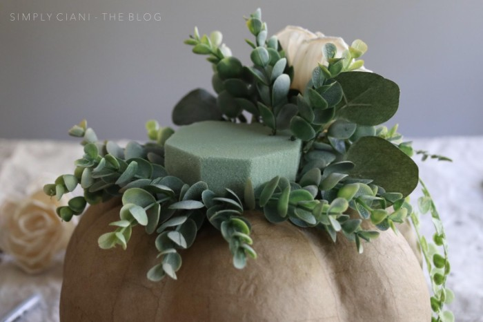 diys for your room, papier mache pumpkin in light beige, with a florist sponge on top, decorated with faux roses, and green plants