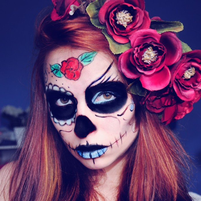 several fake red flowers, decorating the red hair, of a young woman, wearing a sugar skull face paint, in black and blue, red and green