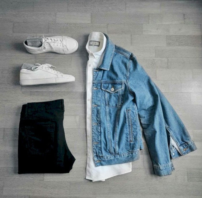 sneakers in white, with striped socks, palced near a folded, blue denim jacket, wardrobe essentials for guys, a white shirt, and a pair of folded black trousers