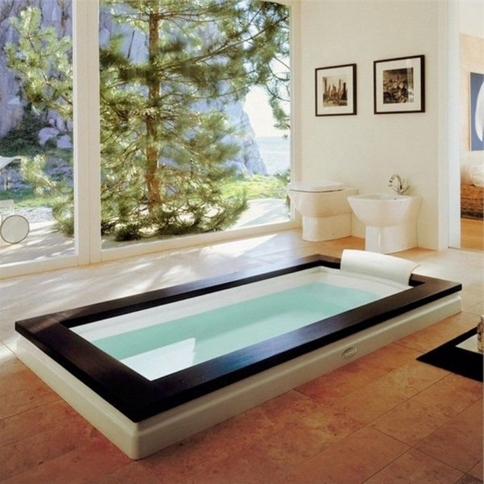 fir tree visible from the large windows, of a bright room, containing a large rectangular batthub, in black and white, spa like bathrooms, beige tiled floor, two framed photos