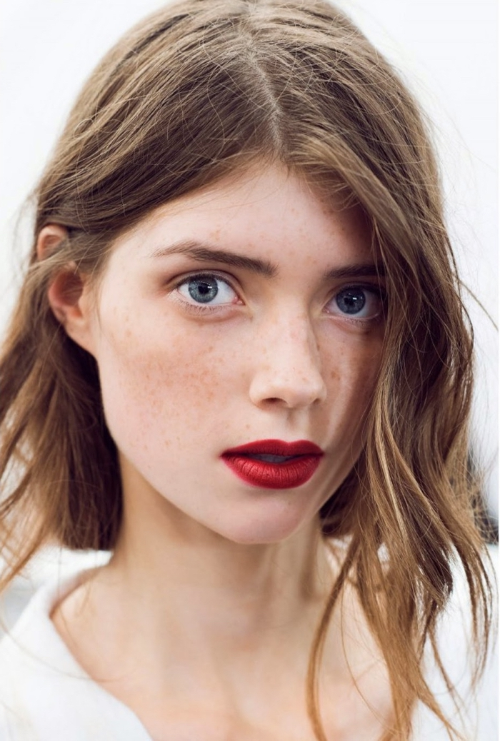 messy light brunette wavy hair, with a middle part, on a pale young woman, with blue eyes and freckles, wearing bright red lipstick