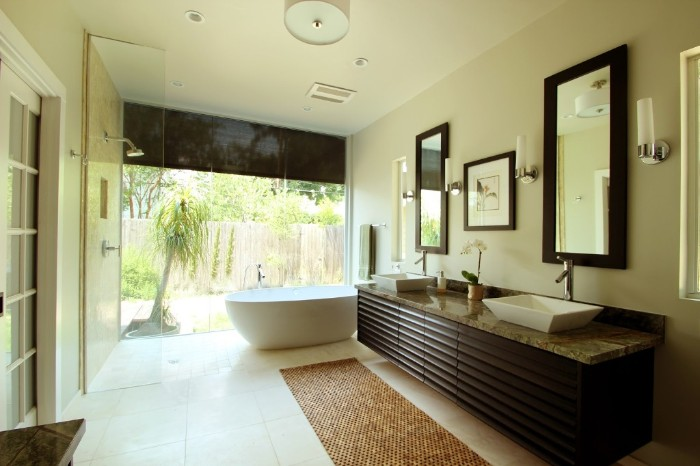 long dark brown cubpoard, with a grey marble counter top, containing two white sinks, master bathroom remodel, white bathtub near a large window, overlooking a garden