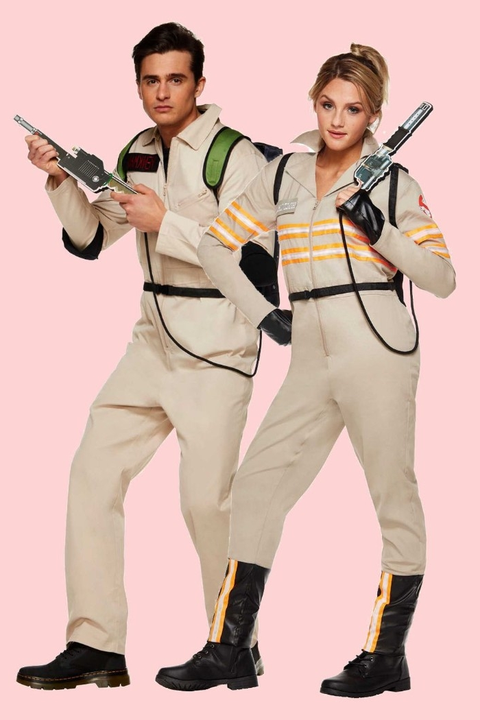 matching beige overalls, with white and orange stripes, worn by a man and woman, holding gun-like weapon props, dynamic duo ideas, ghostbusters themed halloween