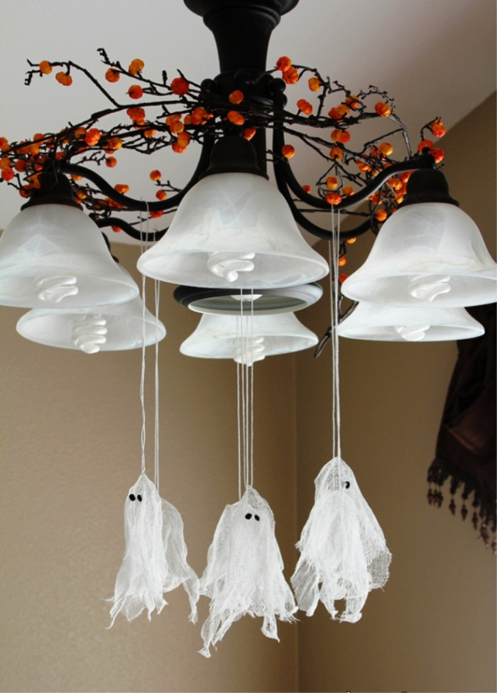 several small ghost ornaments, made from white gauze, scary halloween decorations, hanging on pieces of white string, from a chandelier, decorated with a wreath, made from brown twigs, with orange berries