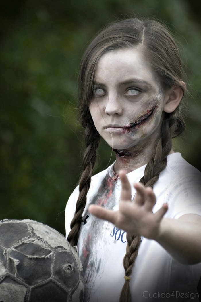 contact lenses in white, worn by a small girl, in a zombie costume, facepaint ideas, with pale skin, and realistic scars