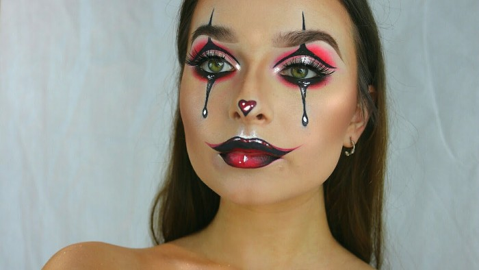 another harlequin inspired face paint, with glossy effect, neon pink eye shadow, and dark red lipstick, with black details, and a small heart shape, on the tip of the nose