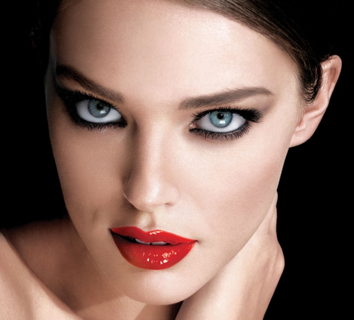 the face of a pale young woman, seen in close up, eye makeup for red lips, blue eyes, outlined with black eye pencil, glossy red lipstick