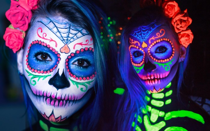 neon colored sugar skull face paint, with glow-in-the-dark details, halloween face paint ideas for adults, worn by a young woman, with dark eyes