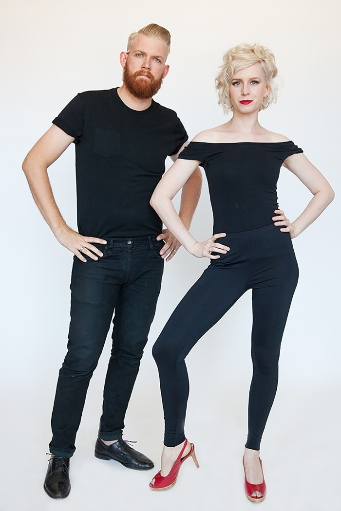 ginger man with a beard, dressed in dark jeans, and a black t-shirt, standing near a blonde woman, wearing black leggings, an off-the-shoulder top, and red high heels, quick halloween costumes, inspired by grease