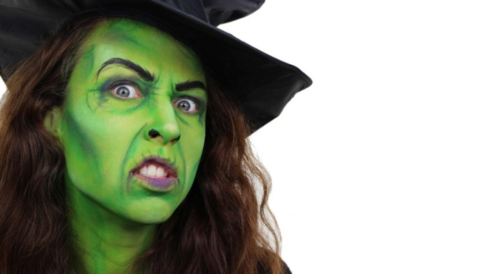 classic witch face paint, brunette woman with long curly hair, wearing green paint on her face, and a black witch's hat
