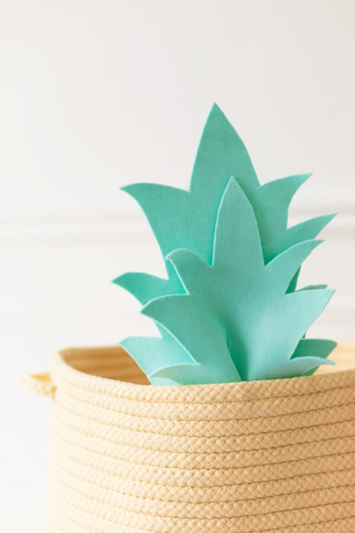 mint green felt cutouts, resembling the crown of a pineapple, attached to the rim, of a pale yellow basket, how to decorate a bedroom, using handmade items
