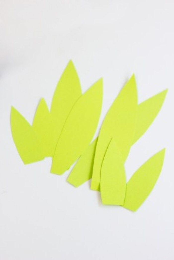 eight light green paper cutouts, shaped like leaves in different sizes, diy bedroom décor, on a white surface