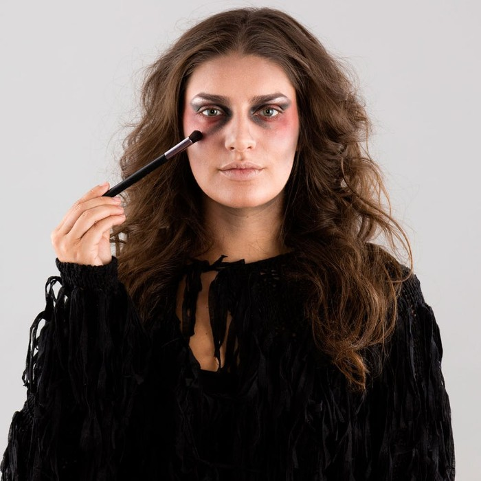 adding dark grey eye shadow, under a young woman's eyes, zombie face paint, step by step tutorial