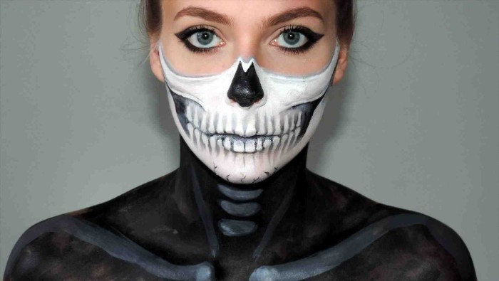 eyeliner in black, worn by a young woman, the lower half of her face is painted to look like a skull, her shoulders are covered in black and grey paint