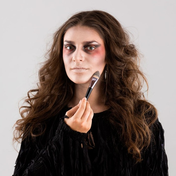 contouring the face of a young brunette woman, using makeup and a brush, zombie face paint, halloween tutorial