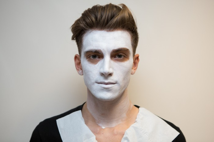 man with brunette hair, styled in a quiff, wearing white paint on his face, facepaint ideas, easy skeleton makeup tutorial